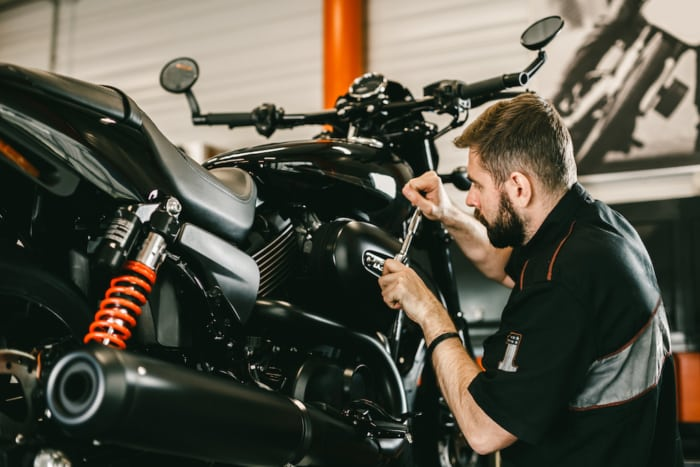 Professional mechanic working screwdriver and motorcycle repairs.